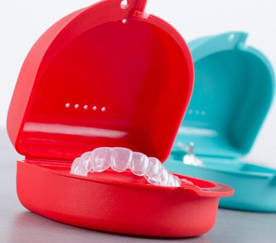 invisalign trays in red and blue cases