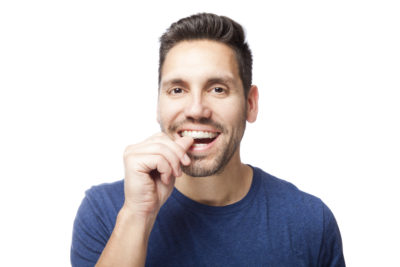A young man with dark brown hair putting his Invisalign clear aligner onto his teeth