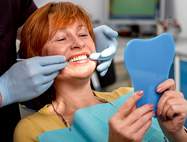 A woman with short red hair smiling as the dentist examines her teeth