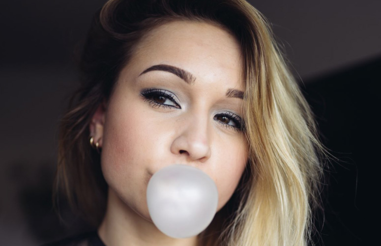 girl blowing a gum bubble