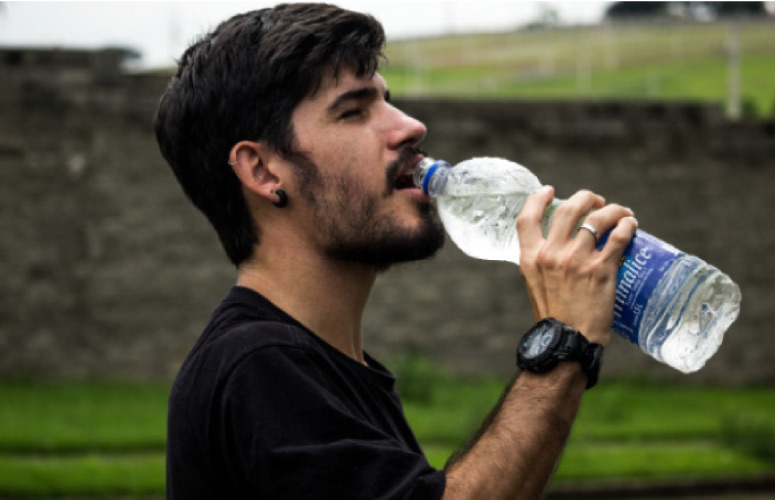 man drinking from a water bottle to benefit his oral health