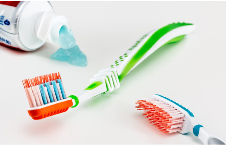 two new toothbrushes and toothpaste