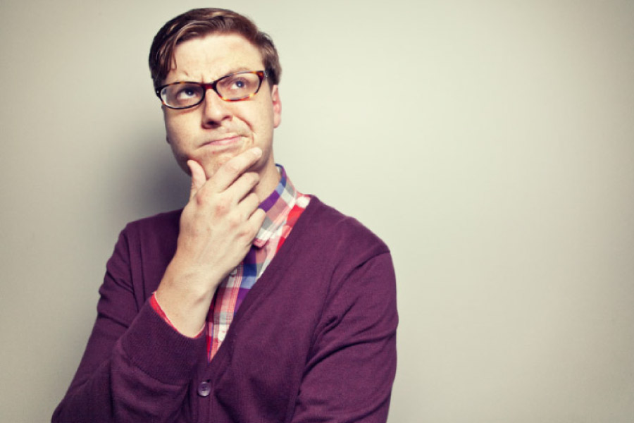 man with glasses holds his chin and ponders how long dental crowns last