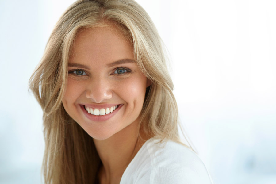 young blond woman smiles to show off her bright, white, straight teeth.
