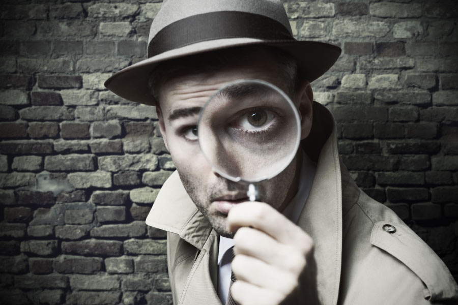 man in a hat and trench coat holds a magnifying glass up to his eye