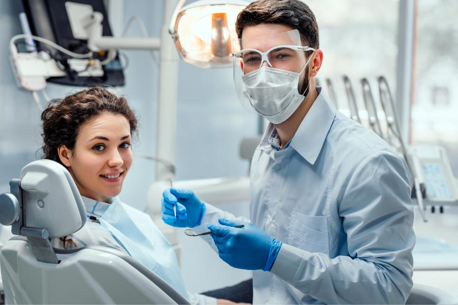 young woman in the dentist chair getting a checkup from a masked dentist